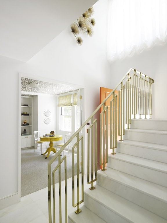 gold and white entryway with gold banister