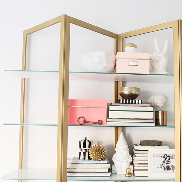 Brass shelving styling with color
