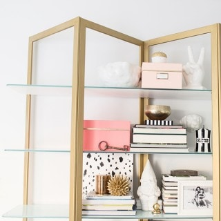 brass shelf styling with neon Kate Spade boxes
