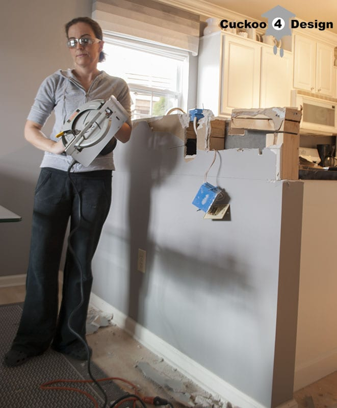 using a circular saw to cut down half kitchen wall to create an island