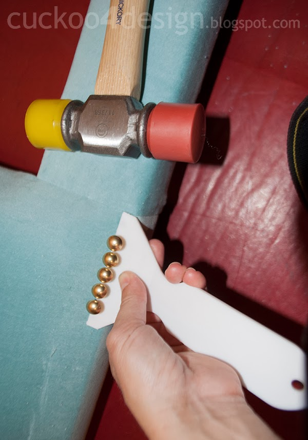 applying brass upholstery nails with a handy tool on DIY fabric headboard edge