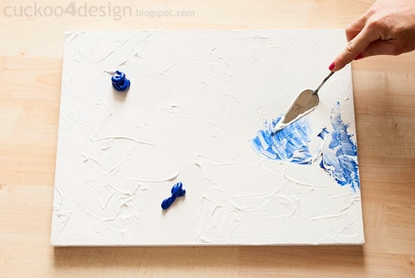 mixing more blue into white acrylic paint with spatula