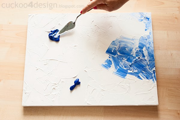 mixing in more blue with spatula on paint canvas