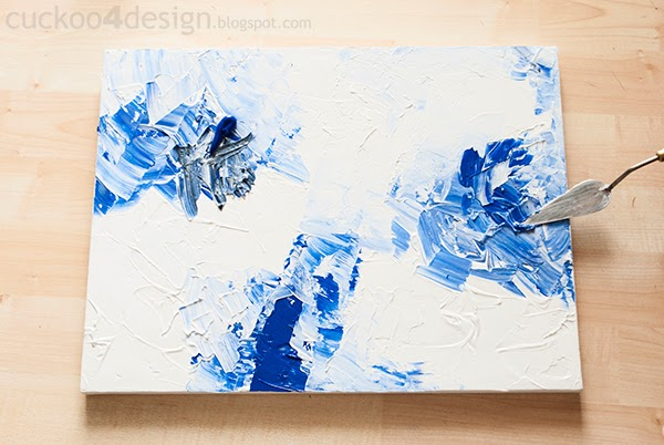 mixing in some black acrylic paint with white and blue on canvas