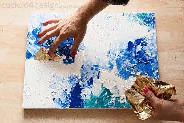 pushing gold foil into wet paint with fingers on canvas