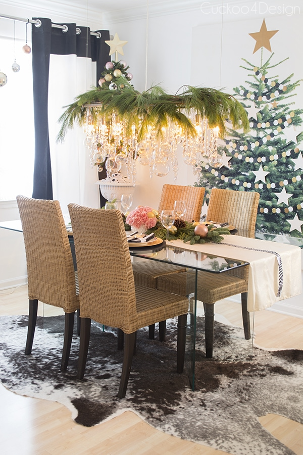 Christmas dining room with clear glass ornaments on chandelier and fresh greenery