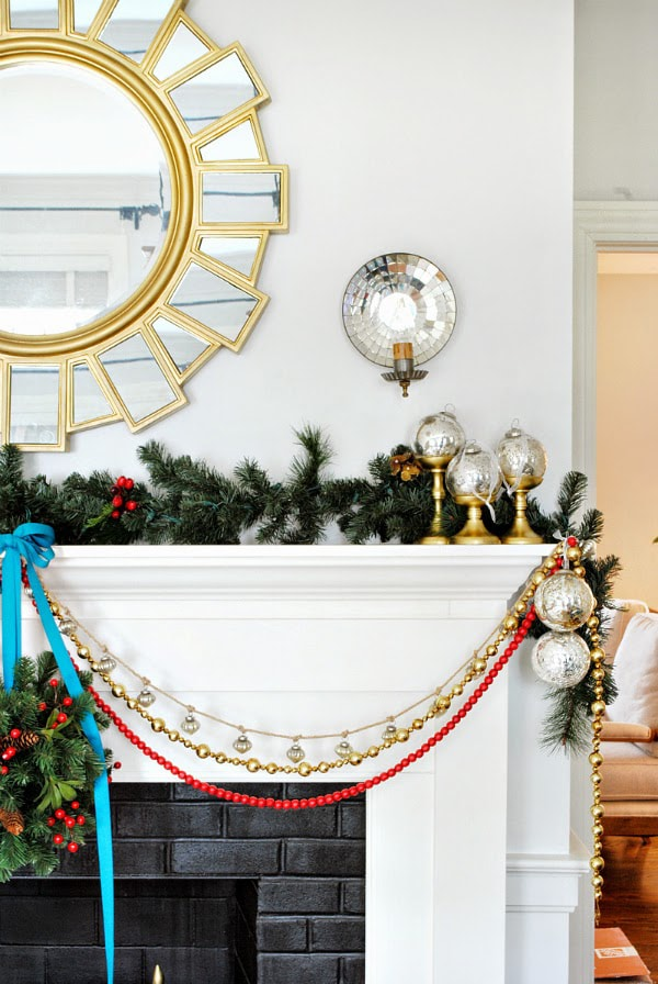 stunning white and gold fireplace with natural greenery