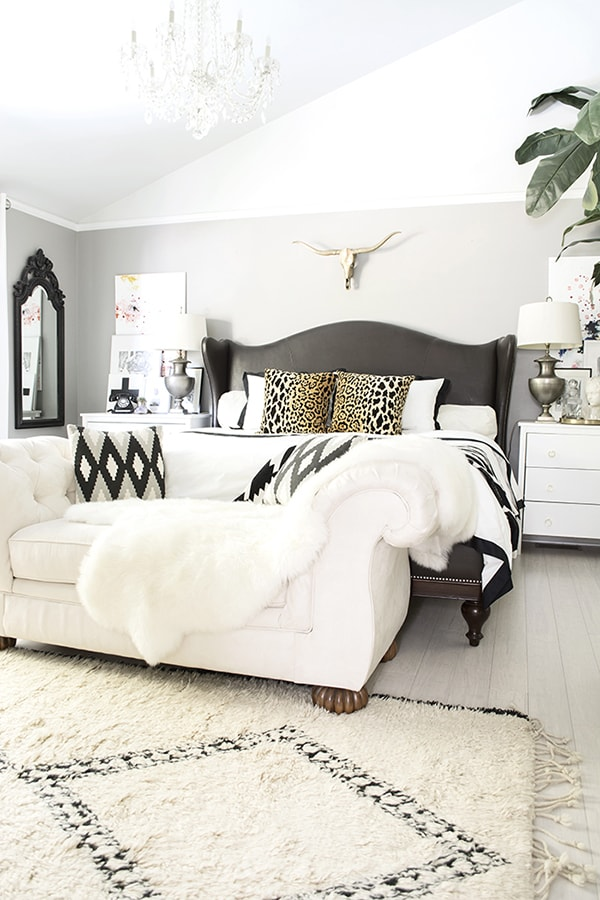 neutral glam boho bedroom with black and white accents, Beni Ourain rug, leopard pillows and banana tree
