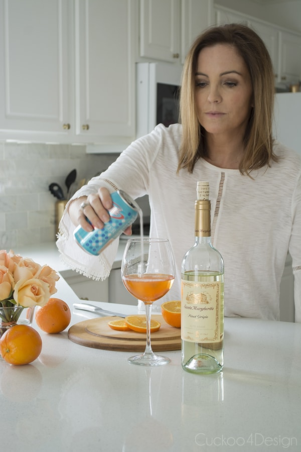 adding seltzer water to Aperol and white wine