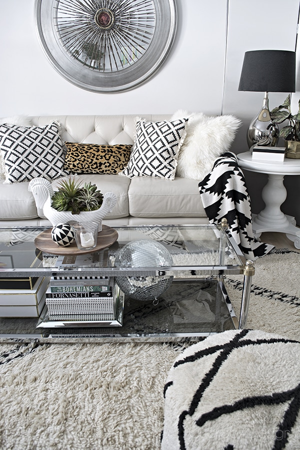 Beautiful Neutral and black and white living room with Beni Ourain rug, disco ball, leather sofa and leopard accent - Cuckoo4Design
