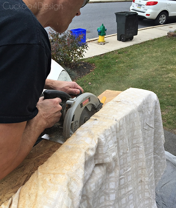 sawing off the bottom of a sofa with a circular saw