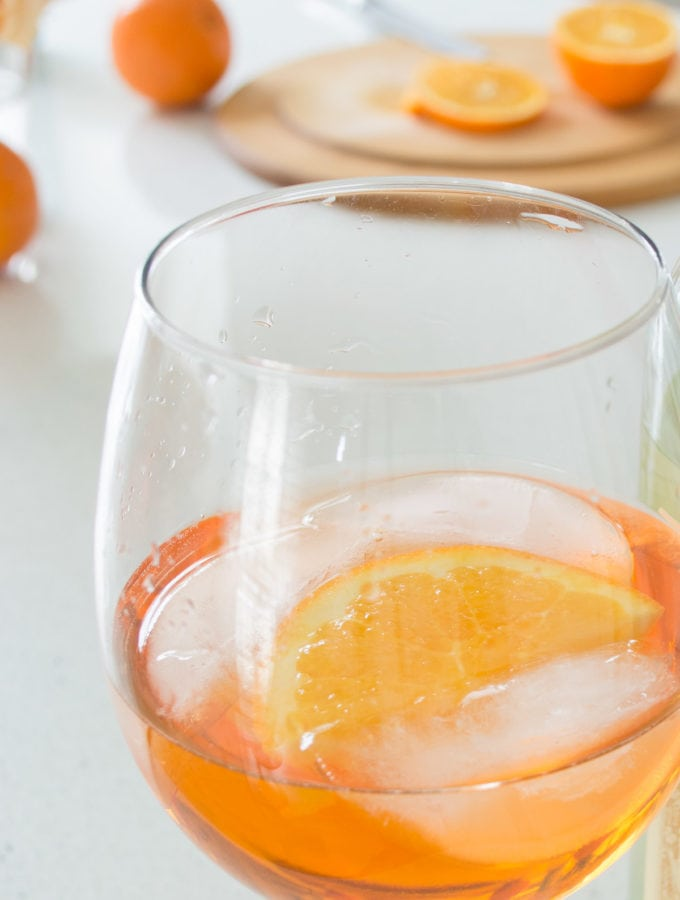 aperol spritz recipe which is aperol with wine, seltzer water, ice and a slice of orange