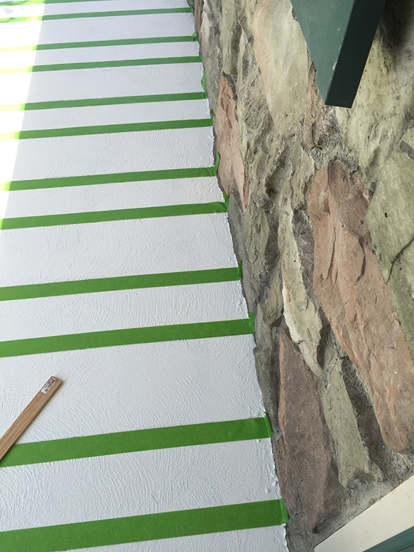 taping the stripes one the painted concrete porch with painters tape
