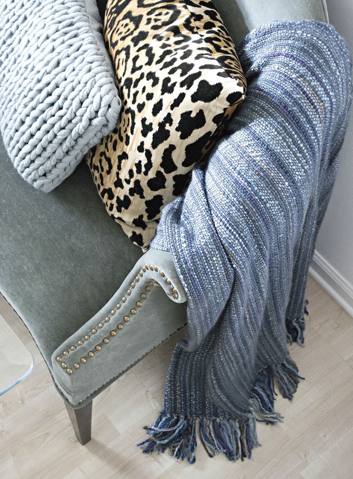 blue dining room chaise with chunky knit pillow, leopard pillow and blue wool throw