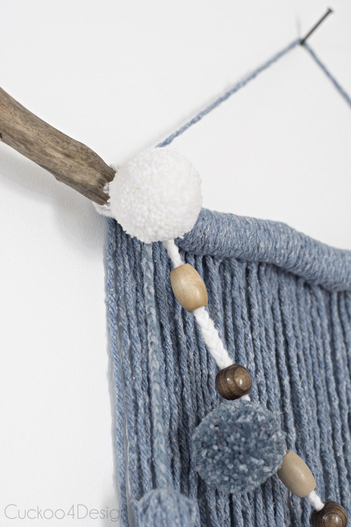 garland tied to mop head yarn wall hanging