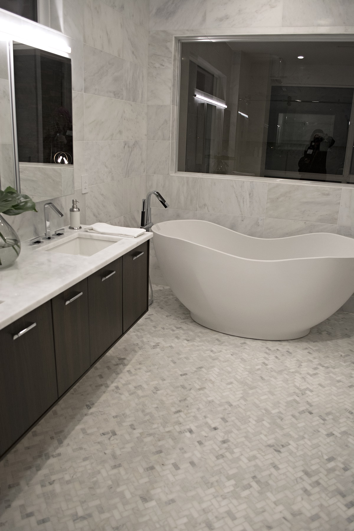 freestanding soaker tub in white marble bathroom