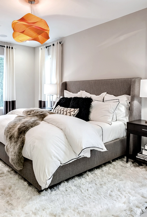 neutral gray master bedroom with orange chandelier