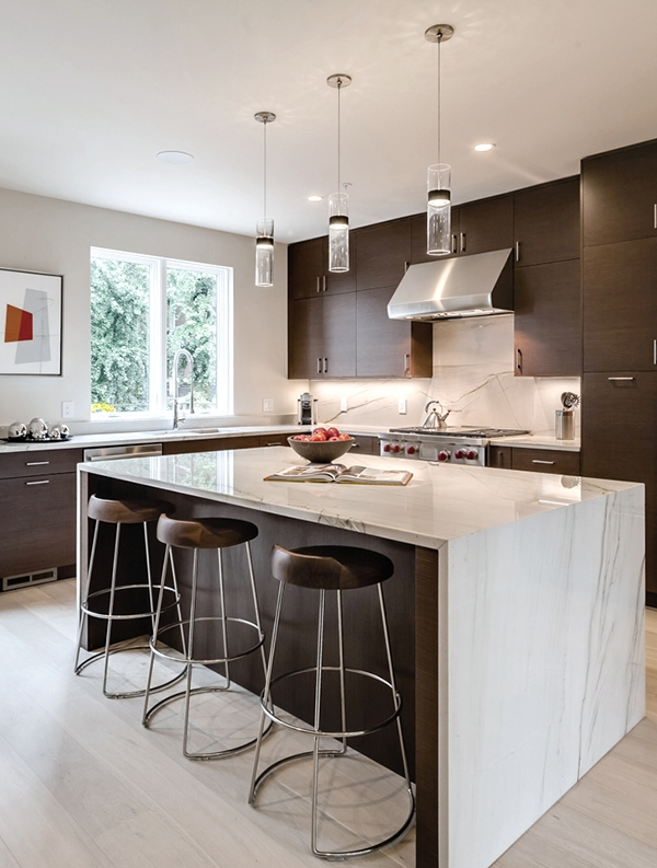 modern dark wood kitchen cabinets with large white marble waterfall island