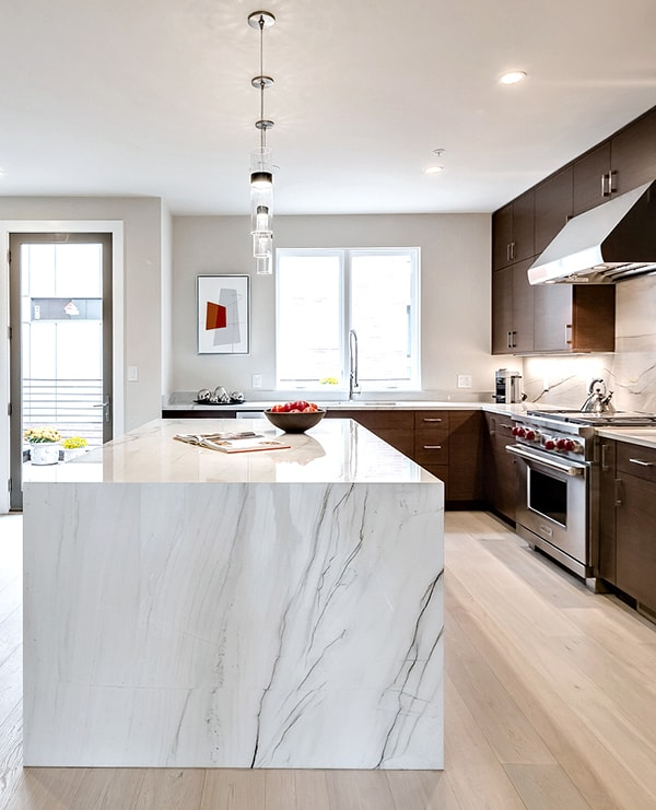 marble waterfall island in modern dark wood kitchen