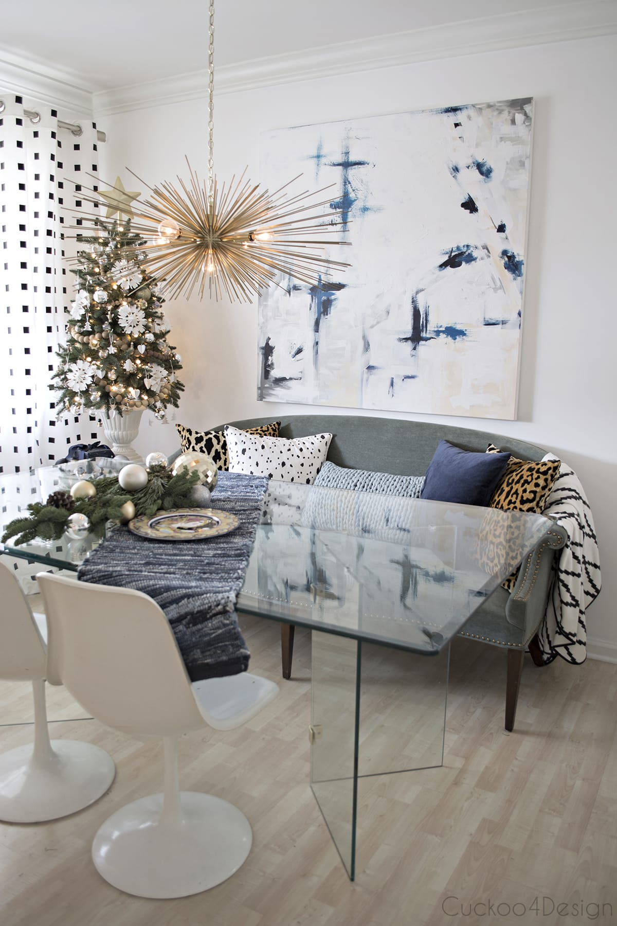 eclectic Christmas dining room with vintage glass table, urchin chandelier and abstract art