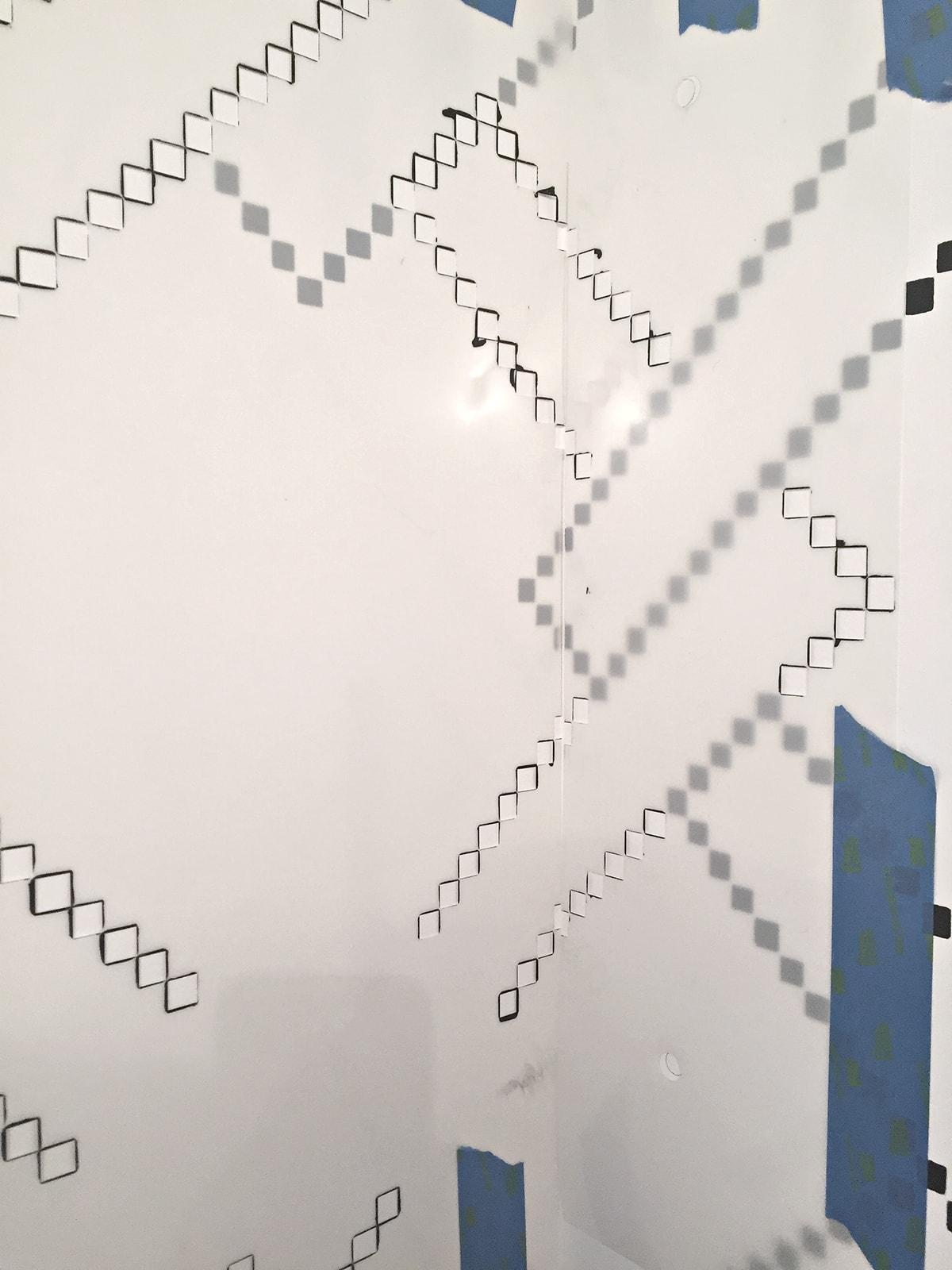 cutting a stencil apart to fit it in a corner
