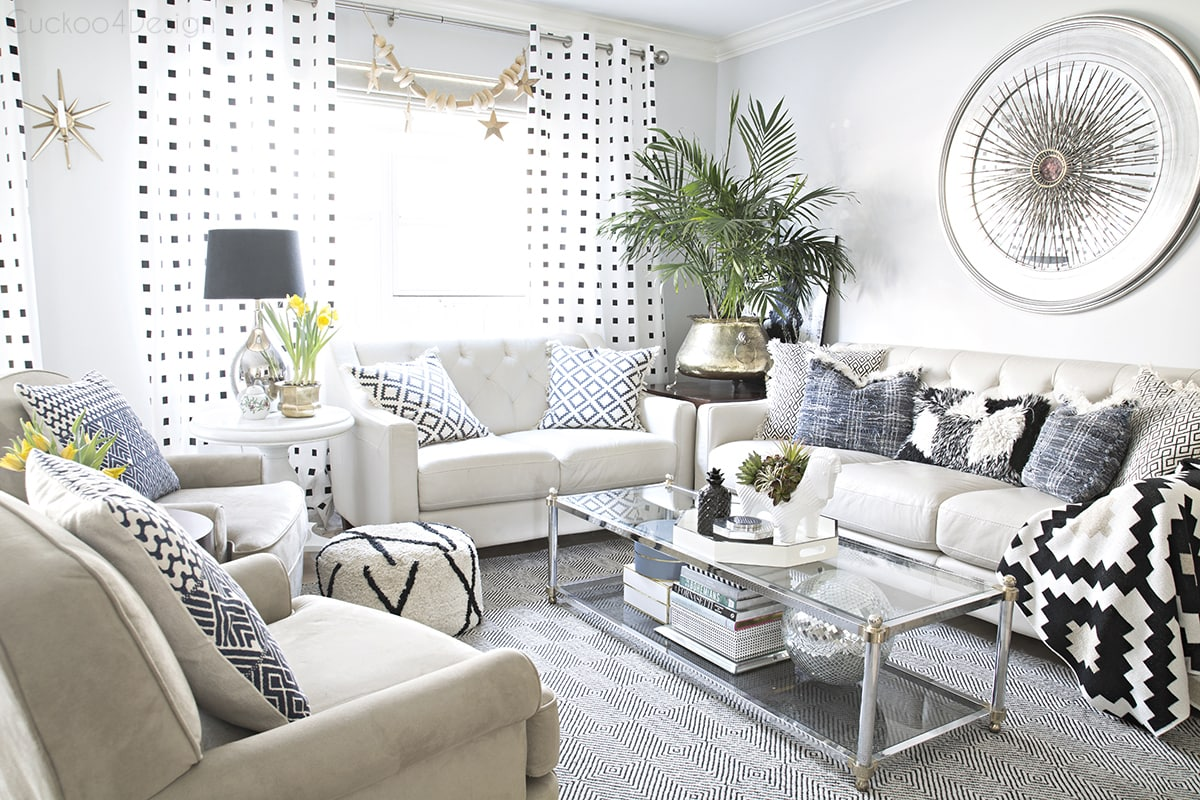 neutral eclectic living room with black and white accents and two arm chairs