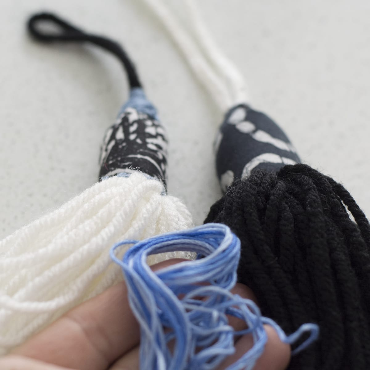 adding detail to yarn tassel with embroidery yarn
