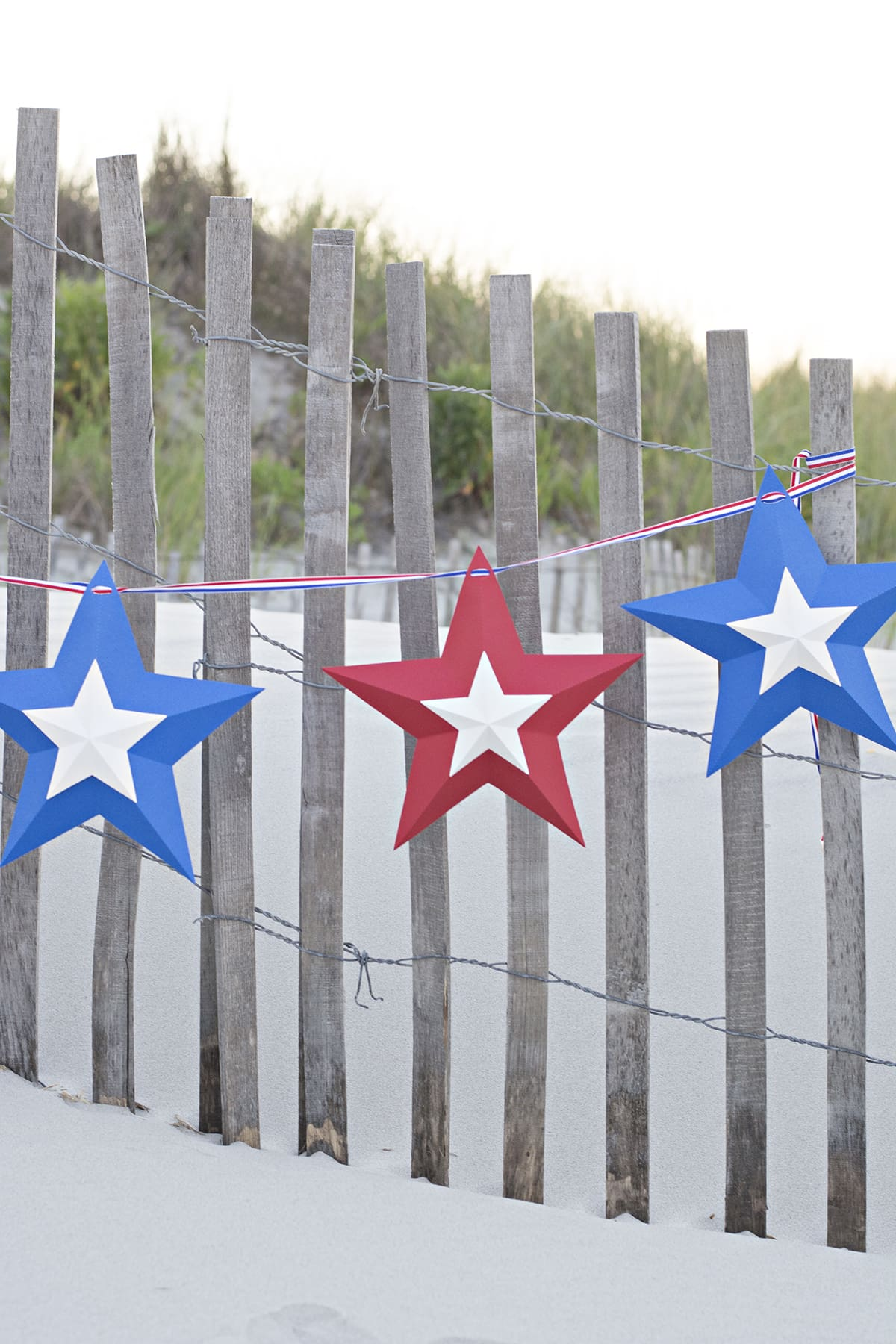 patriotic star bunting hanging on the fence in the beach dunes
