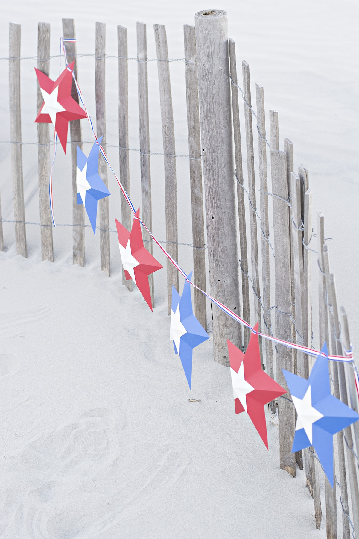 DIY star bunting hanging on the fence in the dunes
