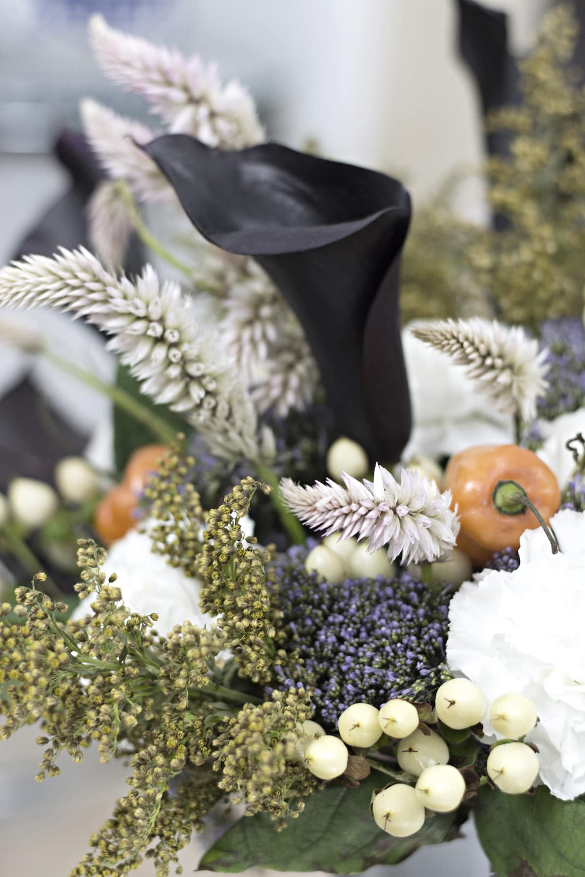 beautiful dark purple and orange flower arrangement for fall with hot peppers