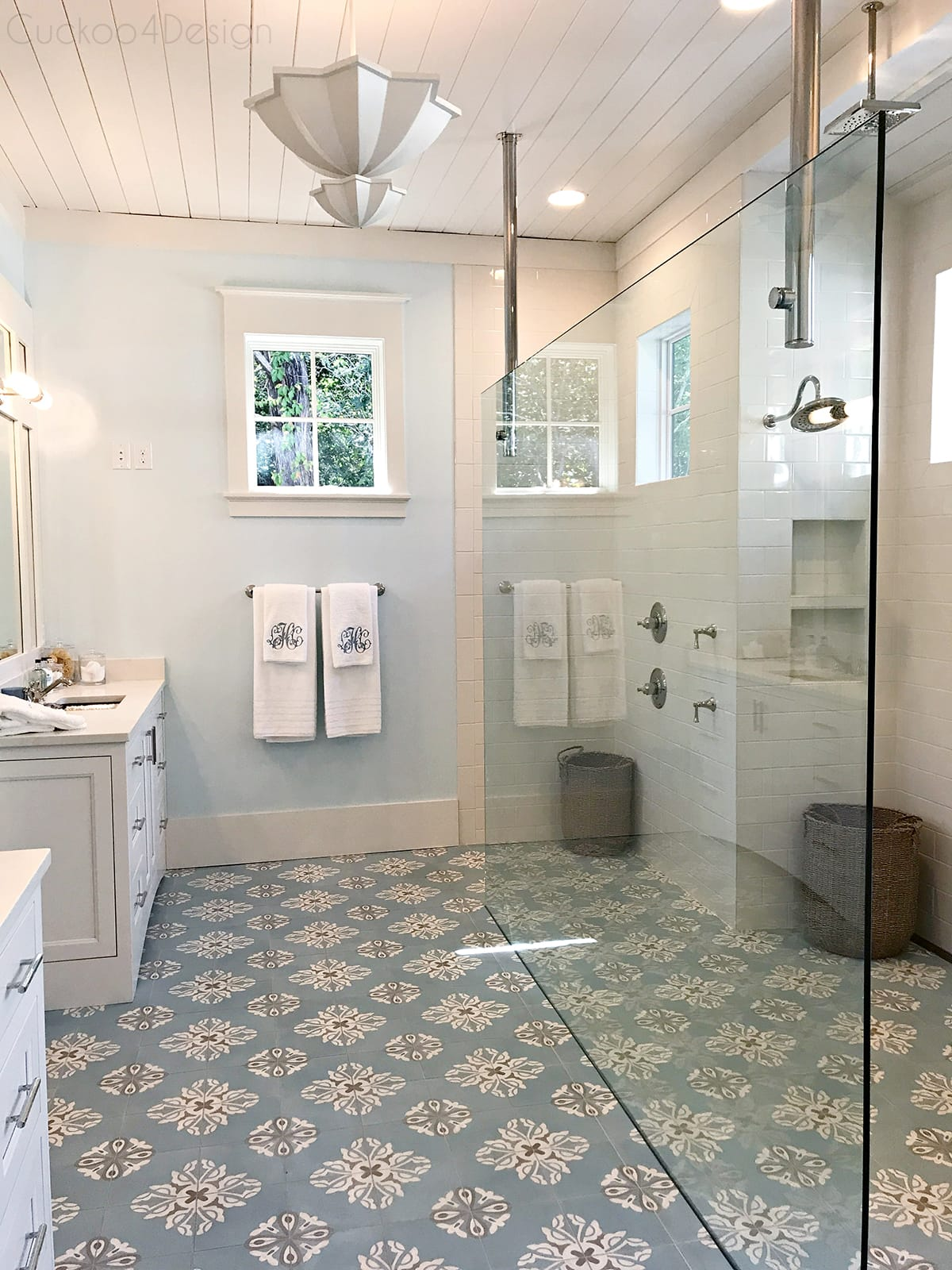 cream and light blue master bathroom with concrete painted tiles andlarge walk in shower with glass wall