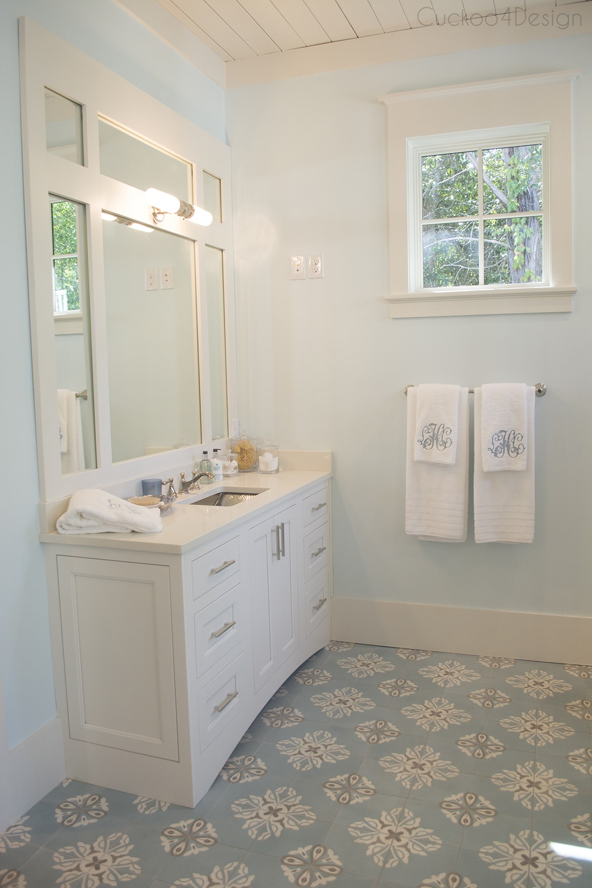 cream and light blue master bathroom with concrete painted tiles
