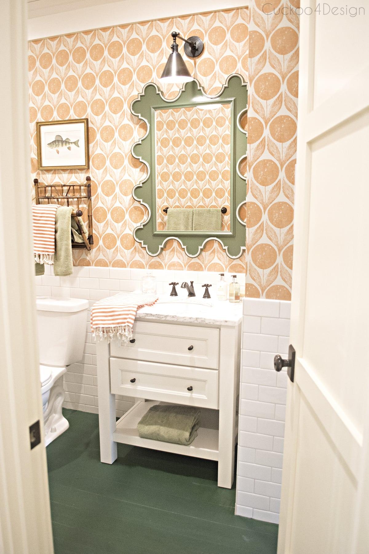 Romo Clementine wallpaper, green scalloped mirror with orange wallpaper in bathroom