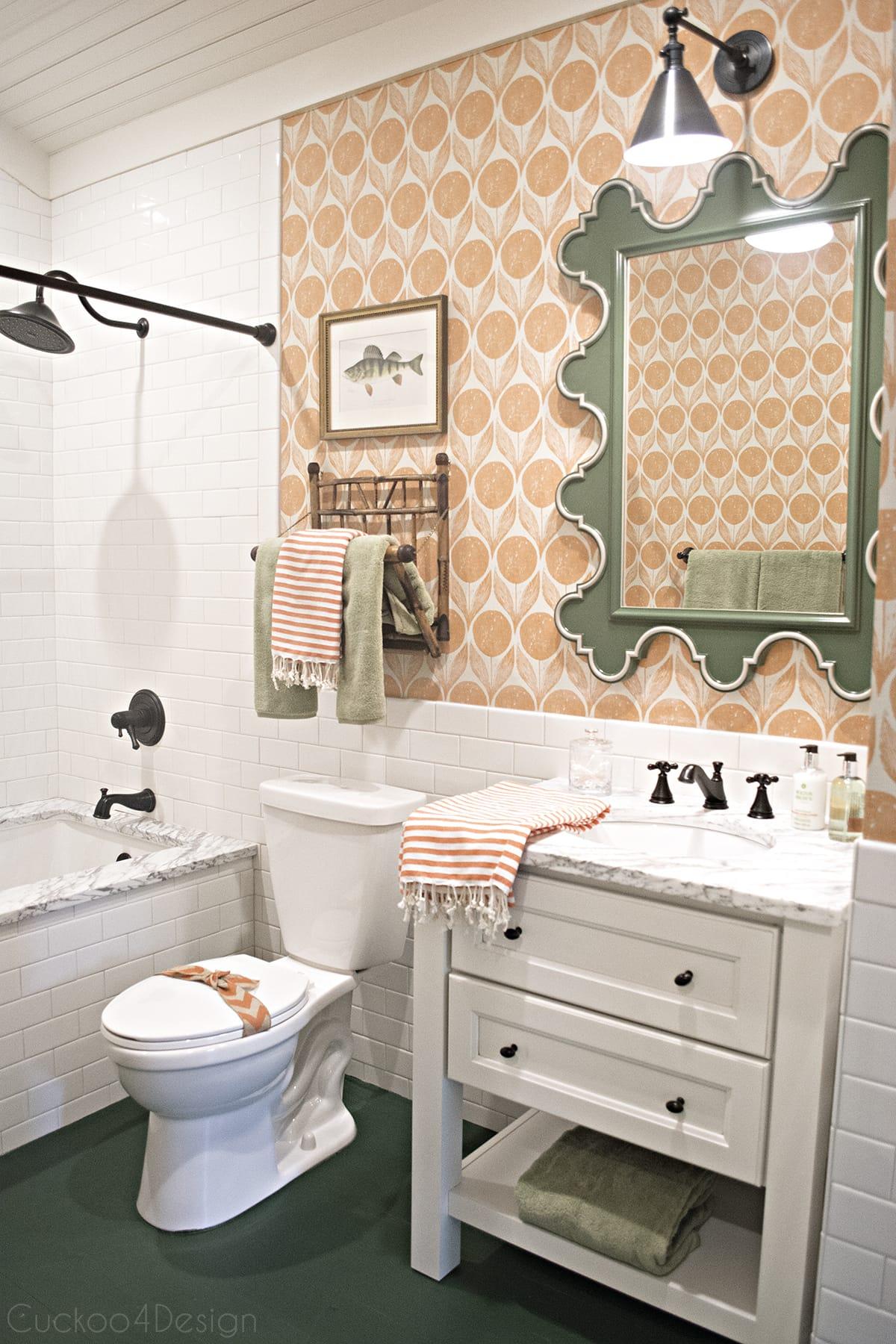 Romo Clementine wallpaper, green scalloped mirror with orange wallpaper and @deltafaucet fixtures in bathroom