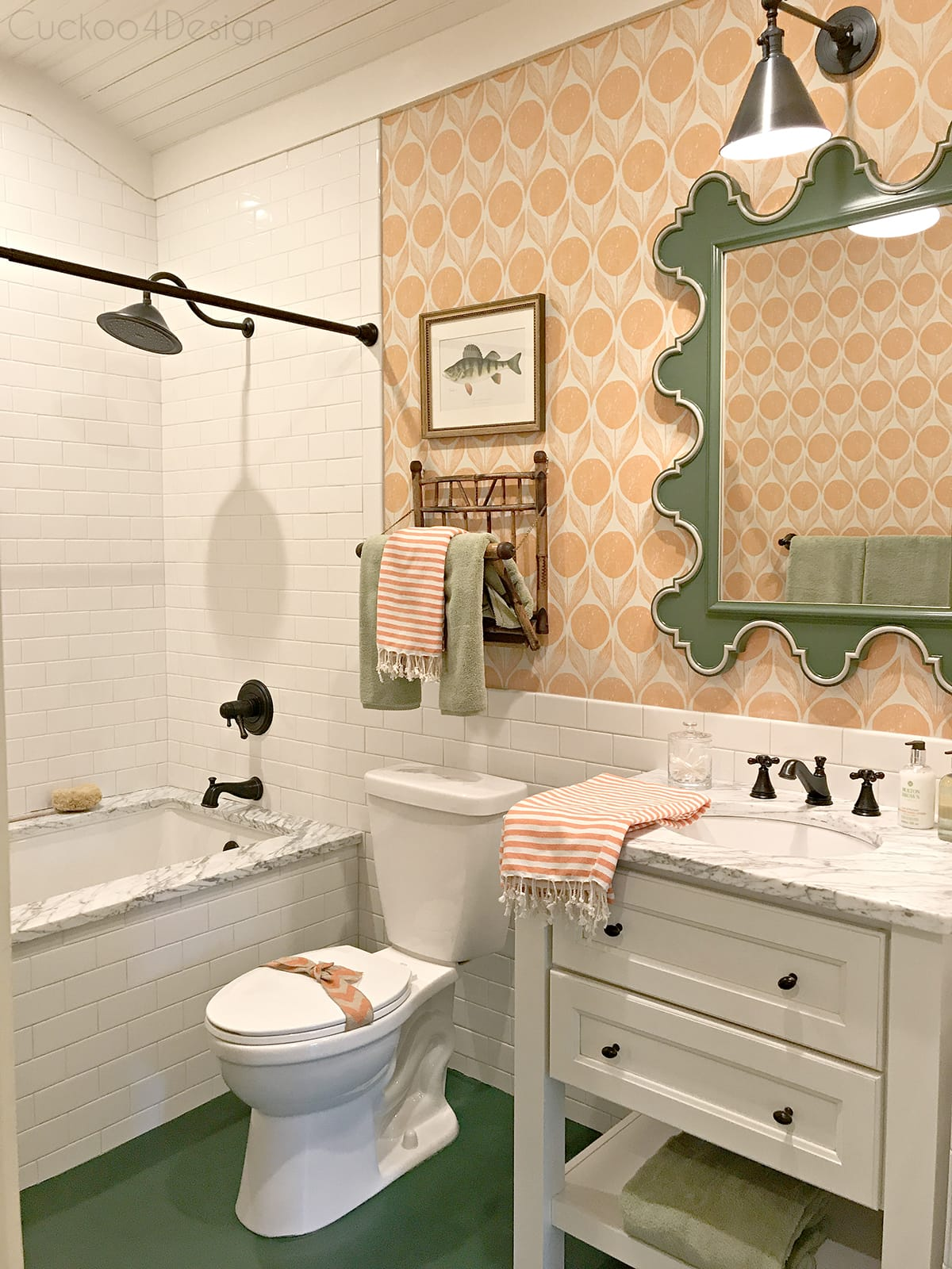 green scalloped mirror with orange wallpaper, hunter green painted wood floor and @deltafaucet fixtures in bathroom