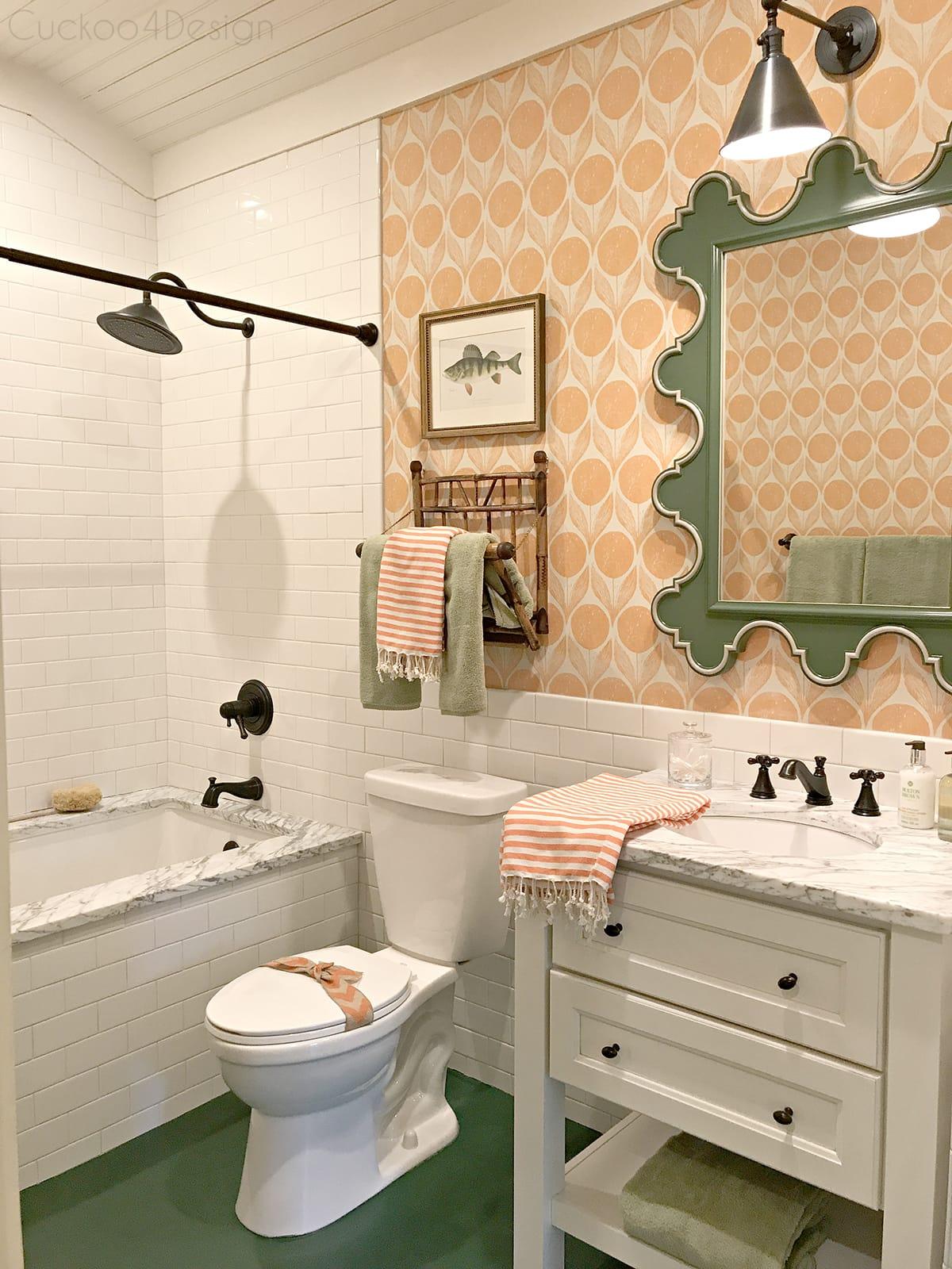 green scalloped mirror with orange wallpaper, hunter green painted wood floor and @deltafaucet fixtures in bathroom