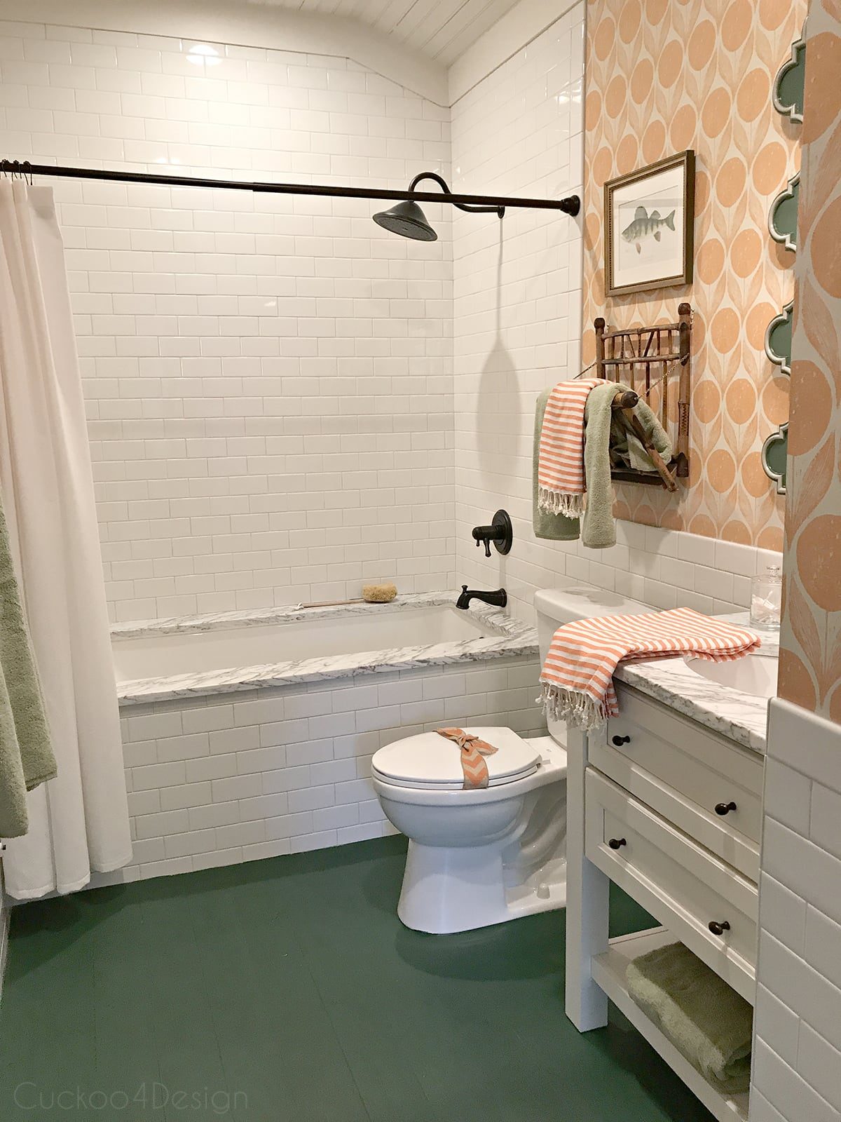 green scalloped mirror with orange wallpaper in bathroom and hunter green painted wood floor