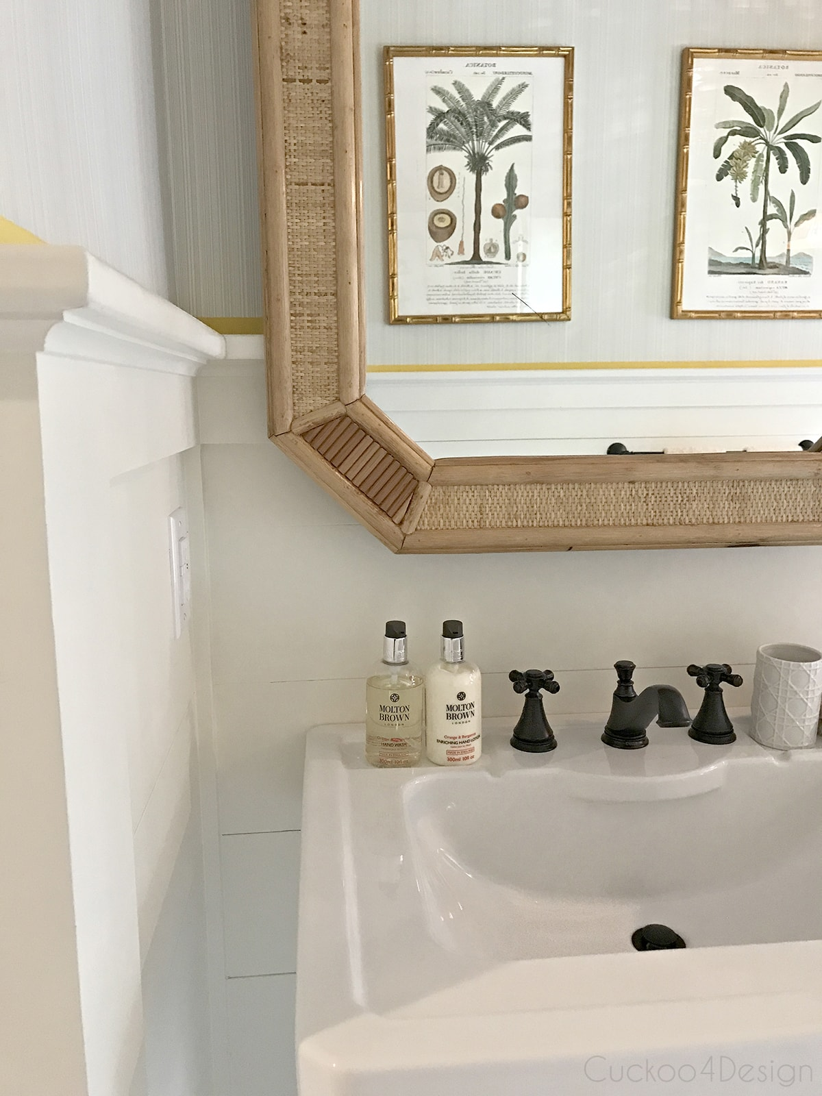 wicker mirror in marble coastal bathroom