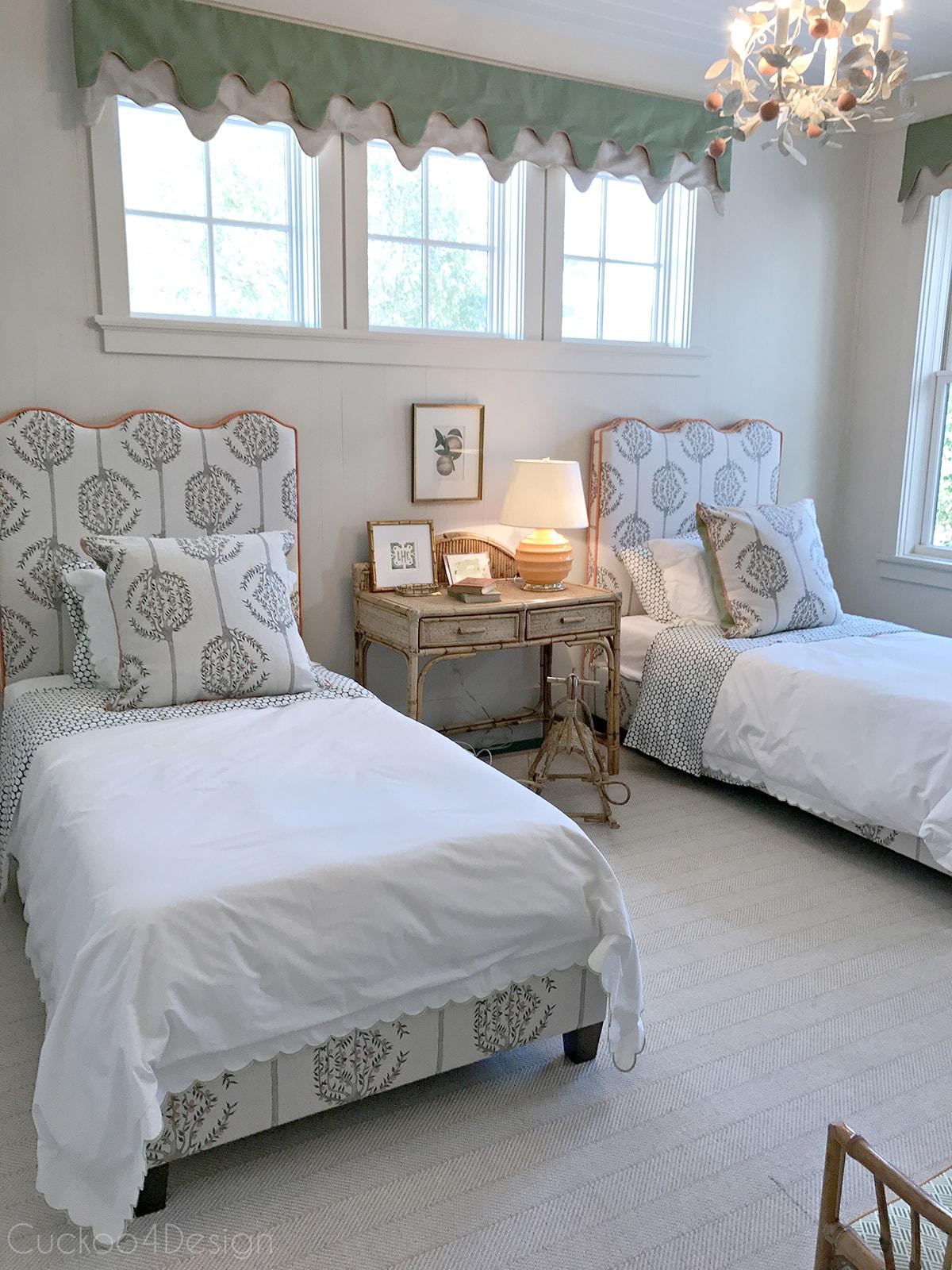 kids bedroom with upholstered headboard, orange trim and vintage wicker furniture