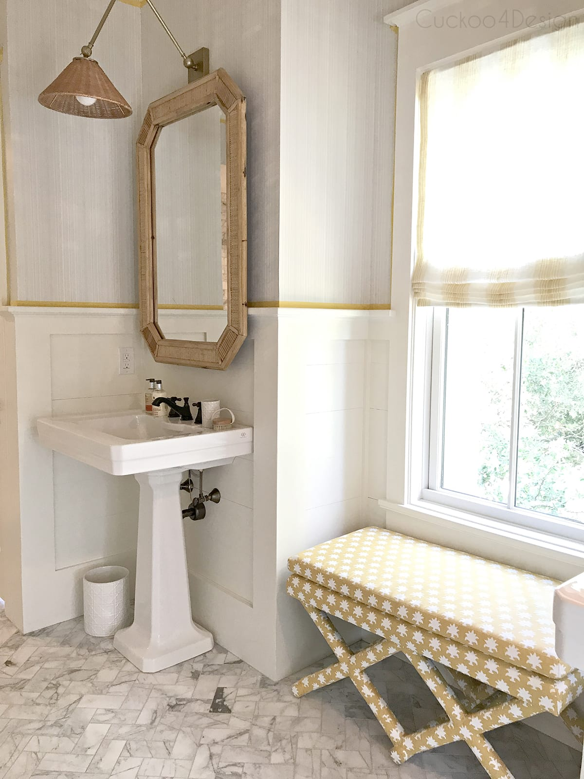 x-bench upholstered with Mally Skok Flora Too Custurd fabric in marble master bathroom and wicker rattan accents