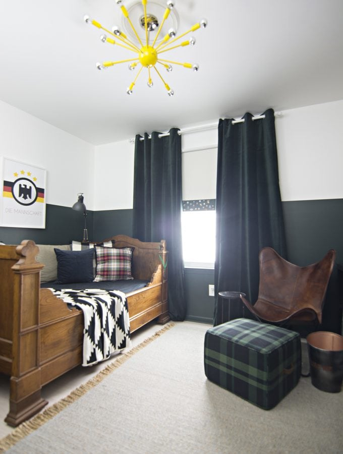 butterscotch leather butterfly chair in sophisticated boys bedroom with dark green walls, mixed plaids and soccer memorabilia and yellow sputnik light fixture
