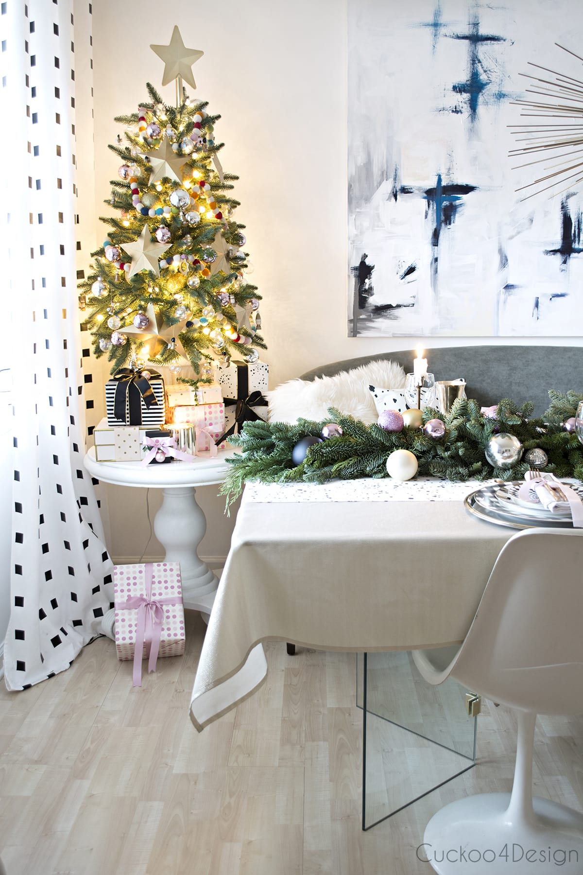 festive table setting with blush, black and white, mixed metallics | urchin chandelier and blue abstract art | pompom throw | tulip chairs and silk velvet settee
