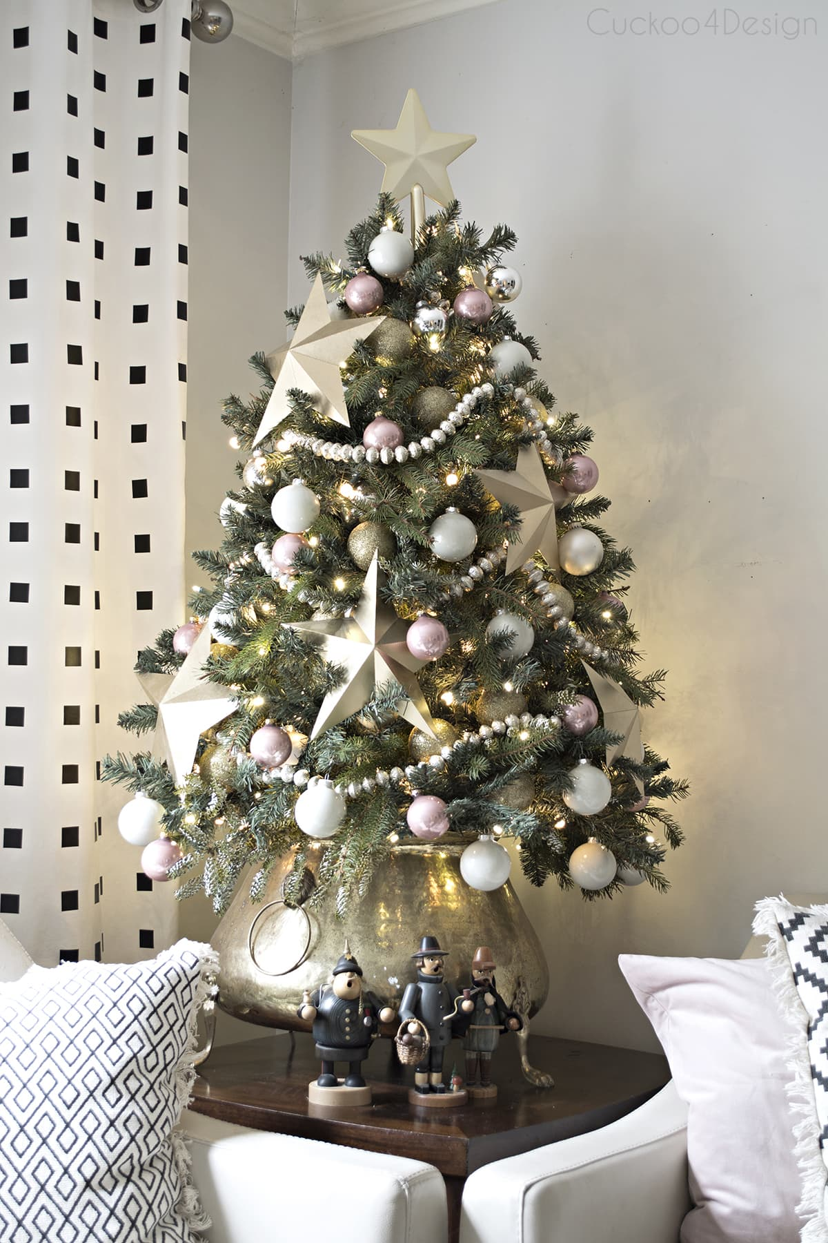 small Christmas tree with large gold paper stars and blush and white ball ornaments in vintage brass pot