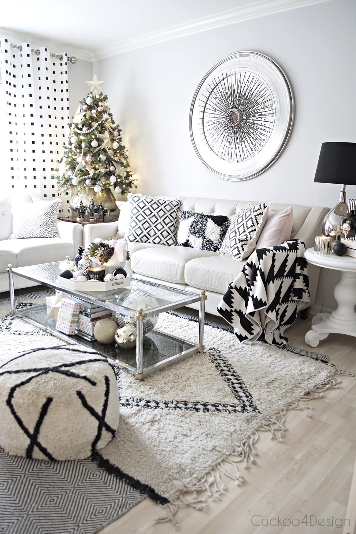 beautiful bohemian eclectic living room with black and white accents, mixed metallics and blush accents | vintage Curtis Jere burst over mirror | Beni Ourrain | small Christmas tree | black and white flat weave area rug