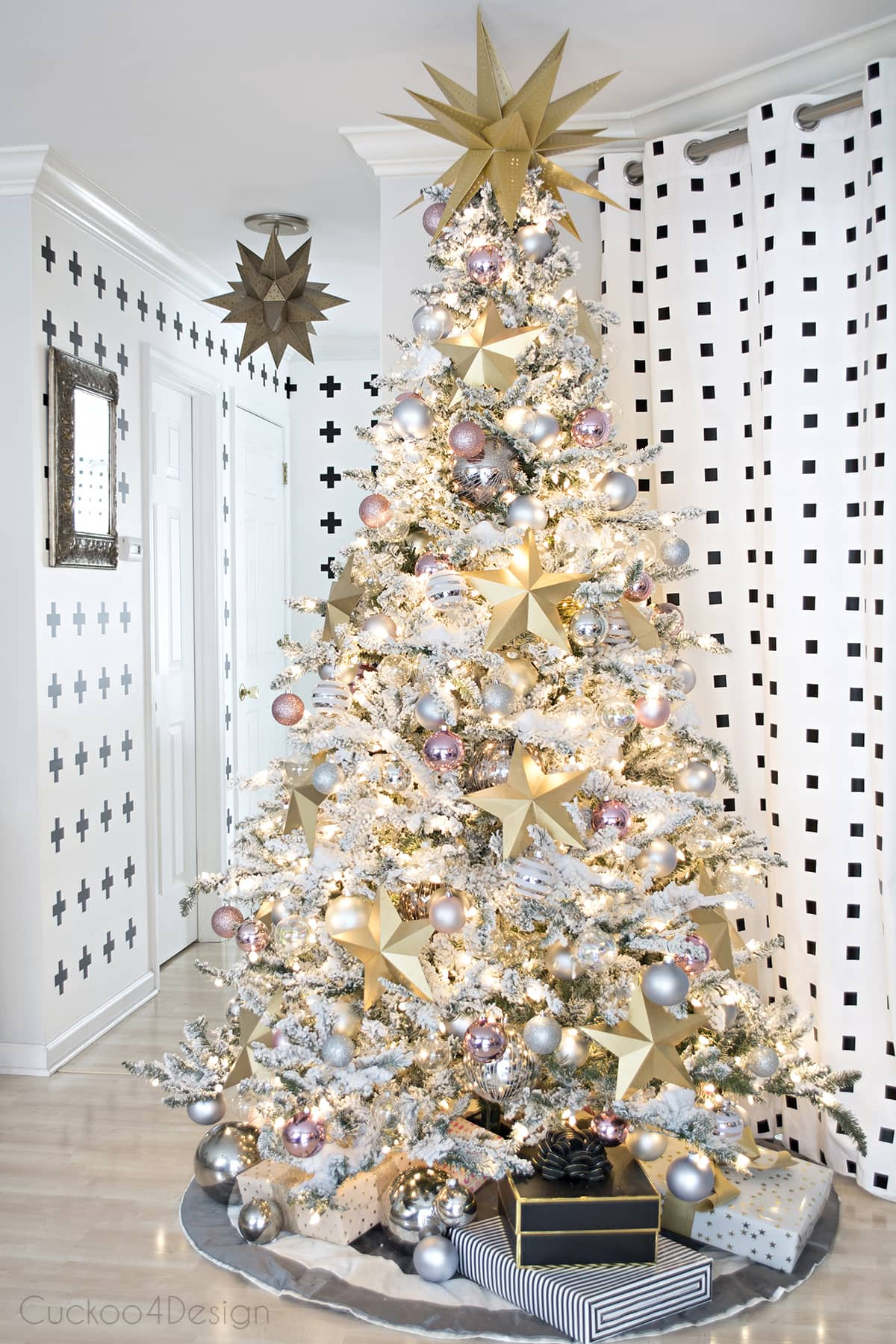 flocked Christmas tree with large gold paper stars and blush and metallic ornaments | black and white curtains