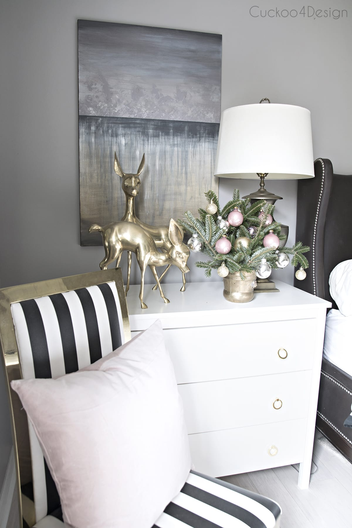 brass, black and white striped chair with blush pillow | brass deer and moody abstract art