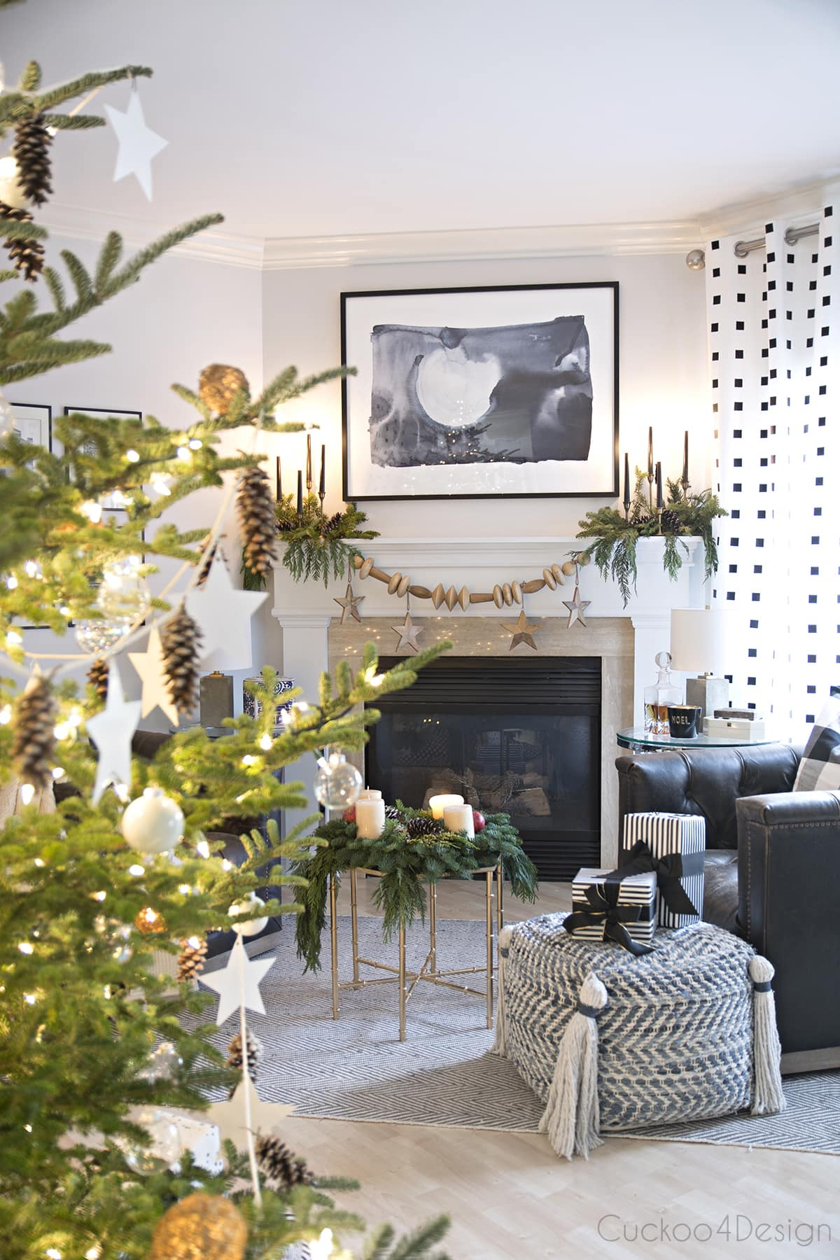 Modern European Eclectic Christmas Tree with pinecones, white stars, clear Christmas balls and white Christmas balls on a real untrimmed fir tree | blue, white and black fireplace area with leather swivel chairs