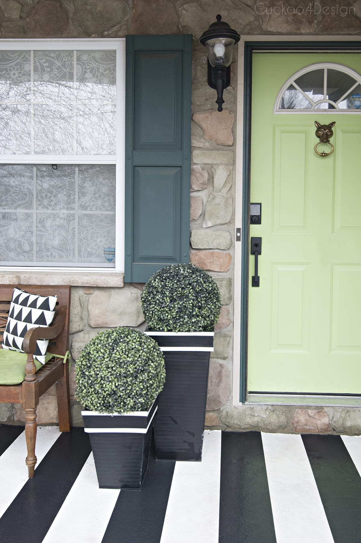 front door with smart dead bolt, lime green door and black and white striped porch