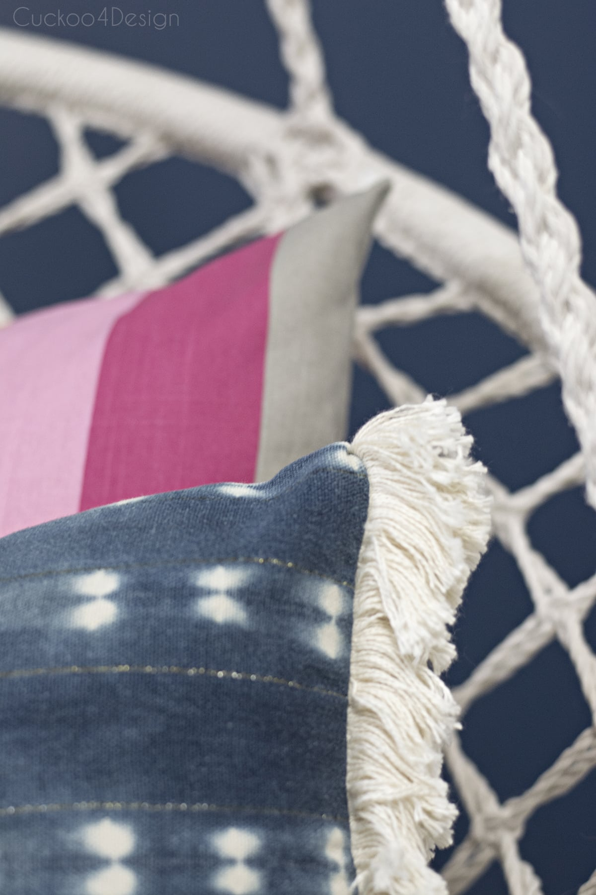pretty hanging macrame chair in girls bedroom with dark blue walls, rainbow pillow and shibori fringe pillow