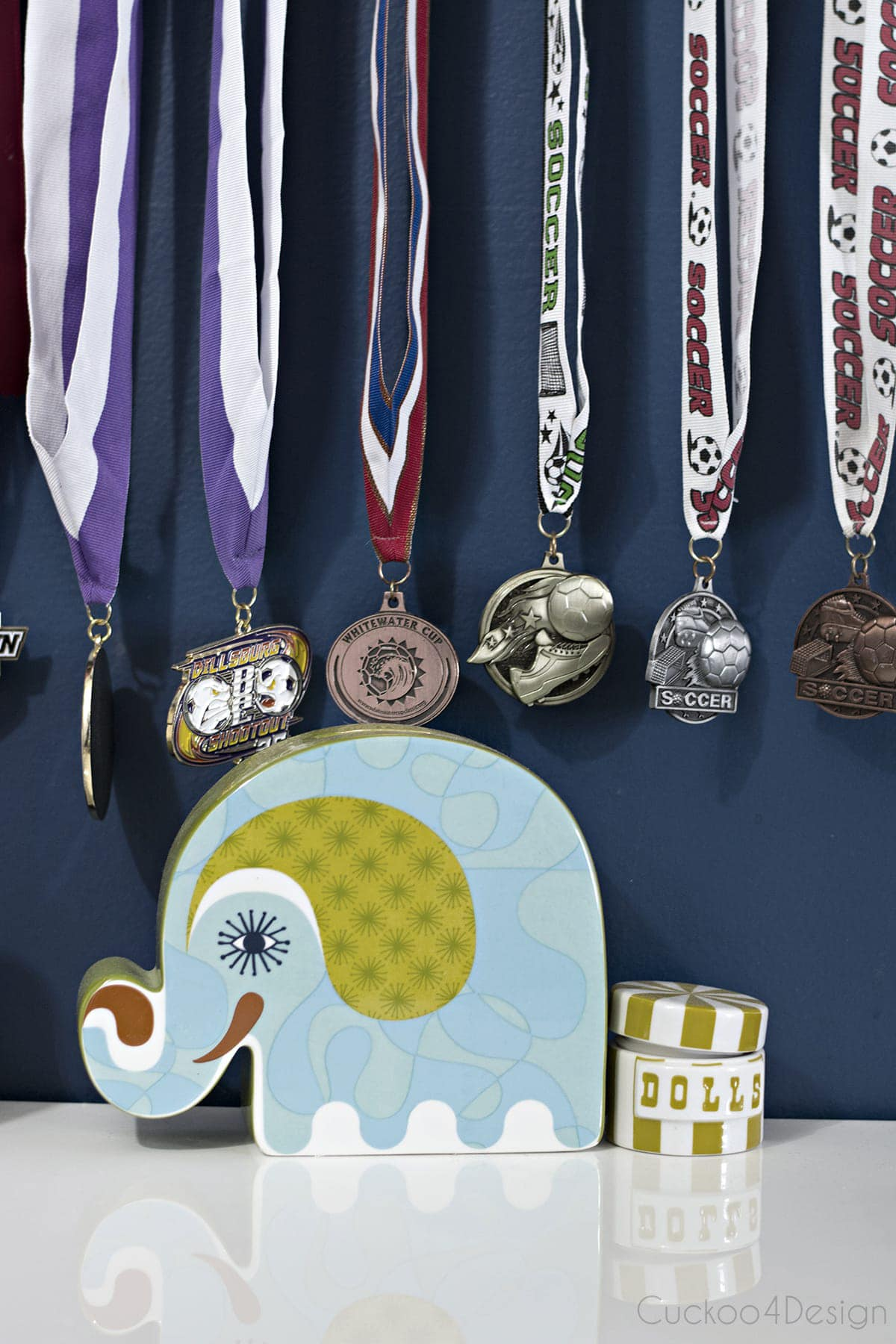 medals hanging above desk on a picture ledge with command hooks in blue girls room